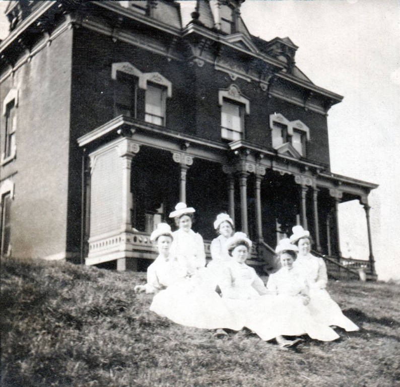 image of women in nursing uniform sitting on a hill beside the old Deaconess Hospital, circa 1904-1097